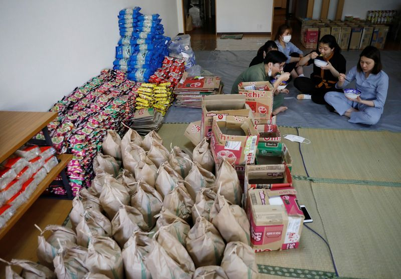 Các lao động Việt ăn trưa cạnh số thực phẩm được chuẩn bị tại chùa Nisshinkutsu ở Tokyo để phát cho người Việt khó khăn trên khắp nước Nhật. Ảnh: Reuters
