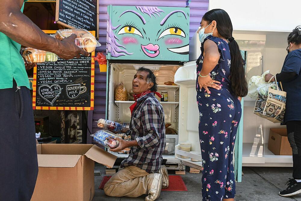 Một người đàn ông lấy thức ăn từ tủ lạnh thân thiện ở Brooklyn. Ảnh: New York Times.