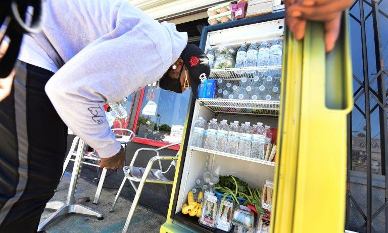 Một người để thêm đồ ăn vào tủ lạnh ở Los Angeles hôm 16/7. Ảnh: AFP