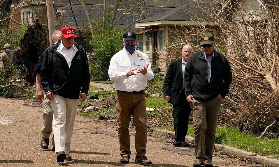 Tổng thống Trump (trái) nghe Thống đốc Louisiana John Bel Edwards (áo trắng) báo cáo về thiệt hại bão Laura, khi thị sát ở Lake Charles, bang Louisiana, ngày 29/8. Ảnh: AP.